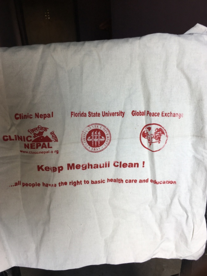 "The back of the reusable bags say, ""Keep Meghauli Clean!"" In larger Nepali cities, such as Kathmandu, trash is piled high on the sides of the streets. Scouts do not want Meghauli to look like those polluted cities."